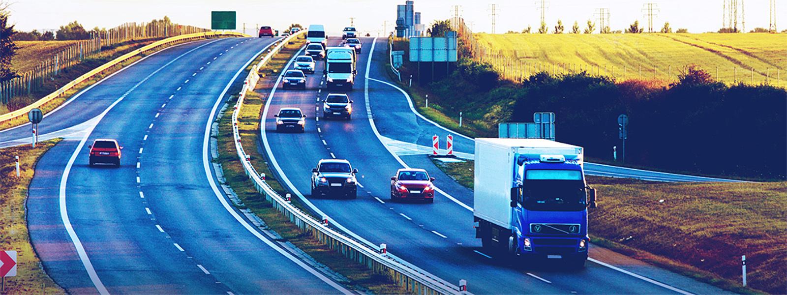 carros e caminhões trafegando por uma rodovia